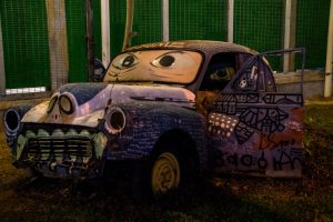 George Town streetart. An old car half dug into the soil and beautifully custom painted